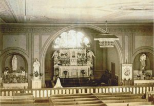 The old church on Rogers Street in the late 1800's. The stained glass window of the Holy family still exists in today's church.